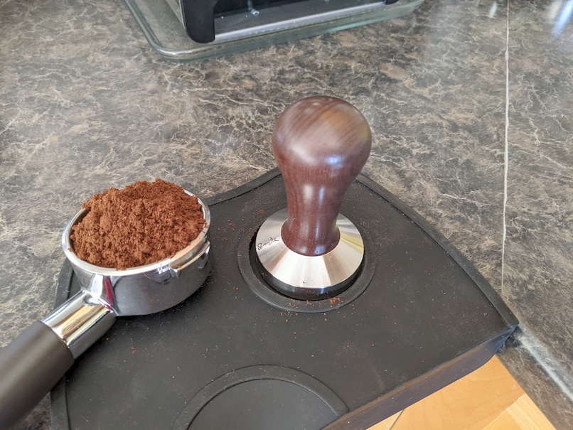 Tamper and ground coffee in portafilter.